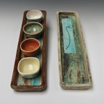 Long oblong stoneware and porcelain trays with small porcelain bowls.