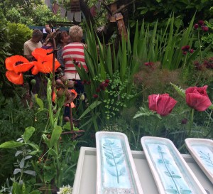 "Trays on a ""bird table"" plinth amongst the flowers"